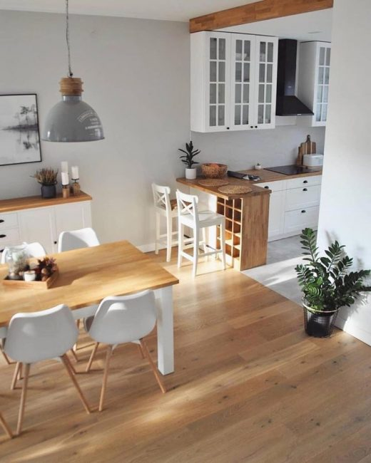 За кухонной зоной расположилась столовая с ламинатом под дерево и обеденным столом.