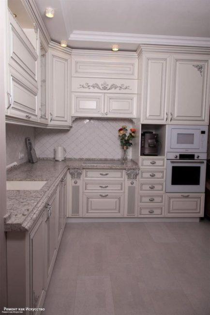 Кухонный гарнитур большой и вместительный. В нем много полочек, шкафчиков и ящиков для кухонной утвари. В гарнитур встроены микроволновка и духовка.