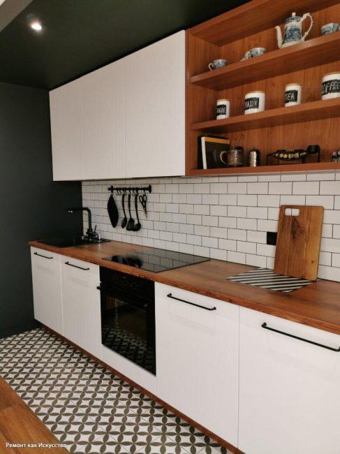 Фартук выложен белым кирпичом. НА полу сочетание ламината и плитки. Ламинат ан полу отлично сочетается с такого же оттенка рабочей поверхностью и открытыми полочками наверху.