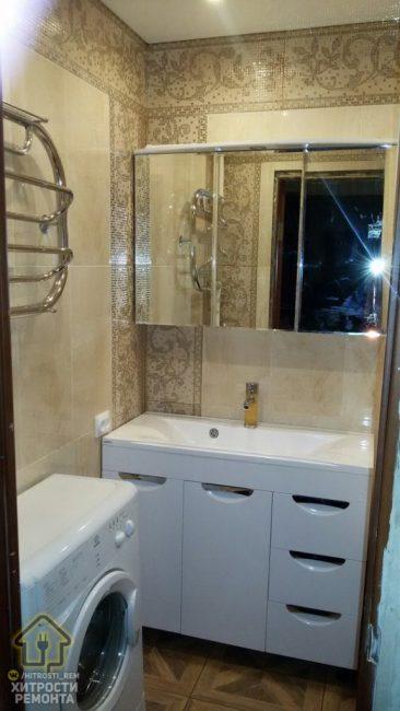 Под полотенцесушителем поставили стиральную машину. У одной из стен поставили большую белую тумбу с умывальником и зеркальные шкафчики.