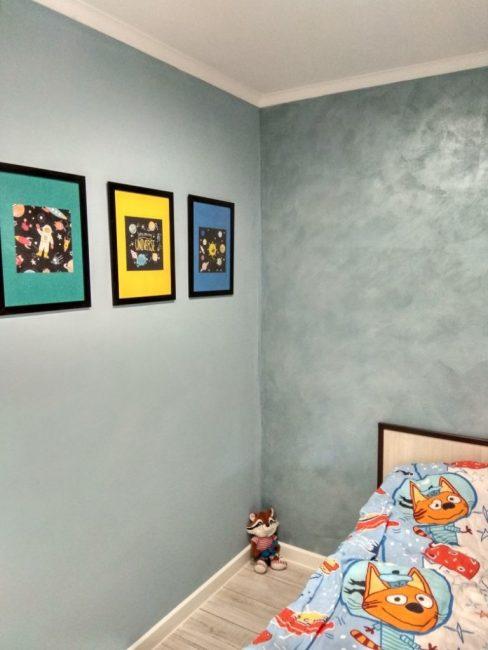 В другом конце комнаты поставили кровать. Обои поклеили светло-голубого цвета. Напротив кровати с одной стороны повесили три ярких тематических постера.