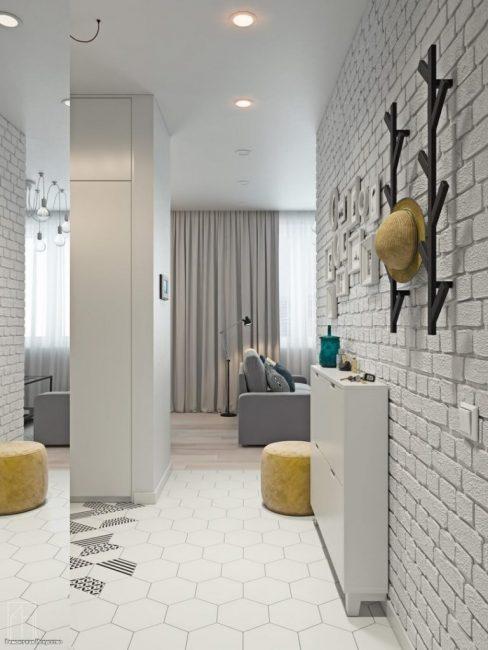 В коридоре стены выложили классическим декоративным кирпичом белого цвета. Довольно популярный и востребованный дизайнерский прием на сегодняшний день.