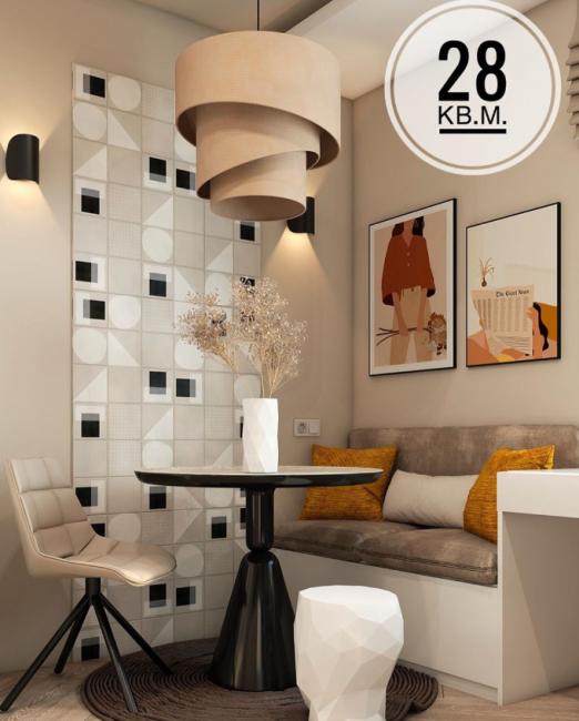 В кухне выделена зона для отдыха и обеда. Это небольшой диванчик и контрастный черный стол круглой формы.