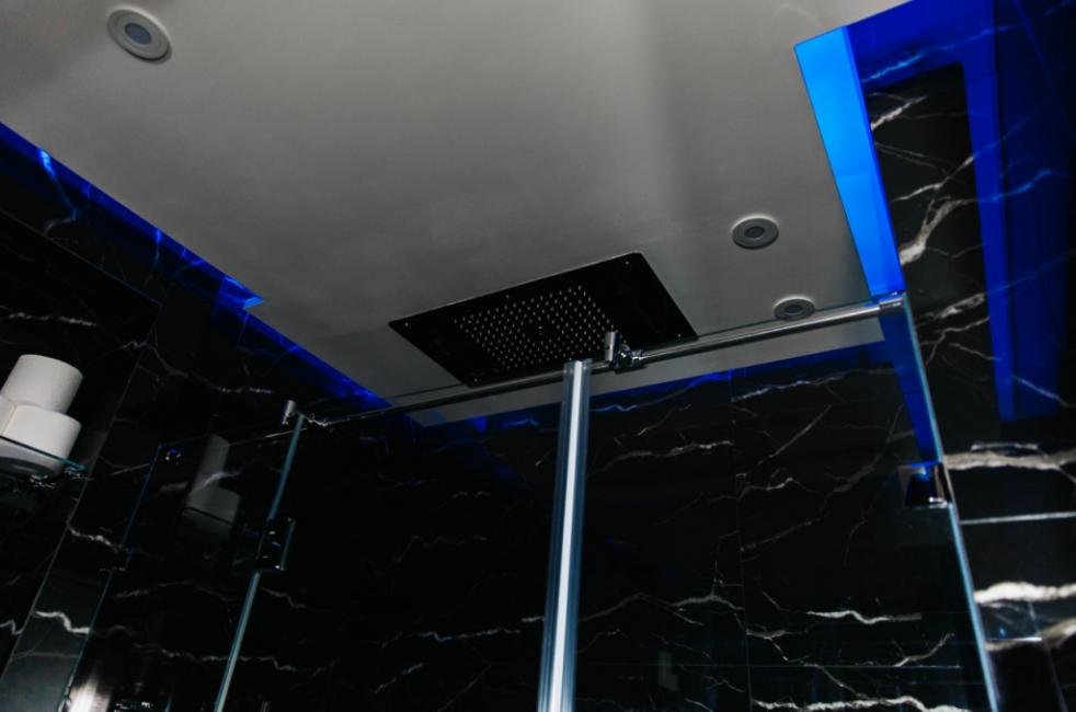 Потолок белый, с оригинальными точечными светильниками. По периметру потолка сделали ярко-синюю неоновую подсветку. Сразу видно, что хозяин этой квартиры — мужчина.