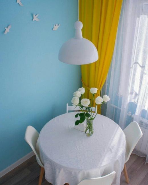 Сочетание небесно-голубого оттенка с желтыми шторами просто непередаваемо. Стены символизируют небо, а портьеры — солнце. Для пущей убедительности над обеденным столом наклеили белых бумажных птичек.