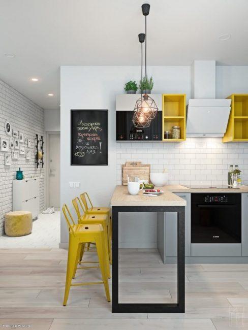 """С кирпичиками на стене в коридоре перекликается фартук на кухне, сделанный из """"кабанчика"""". Чтобы разделить гостиную и кухню, между ними поставили барную стойку с высокими ярко-желтыми стульями."""