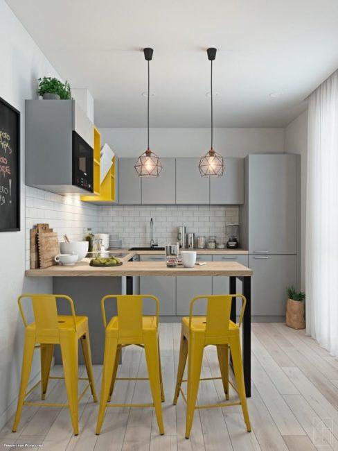 Из освещения — два подвесных потолочных светильника над барной стойкой. Кухонный гарнитур серого оттенка, выполненный в стиле минимализм.
