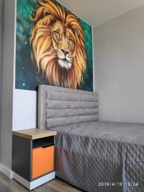 Главным украшением комнаты служит огромная виниловая наклейка с изображением льва. Ее поместили над изголовьем кровати.