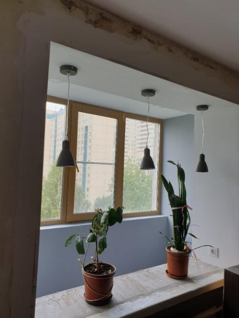 Подоконник окна будет выполнять роль барной стойки. Здесь установили освещение в виде трех подвесных светильников.