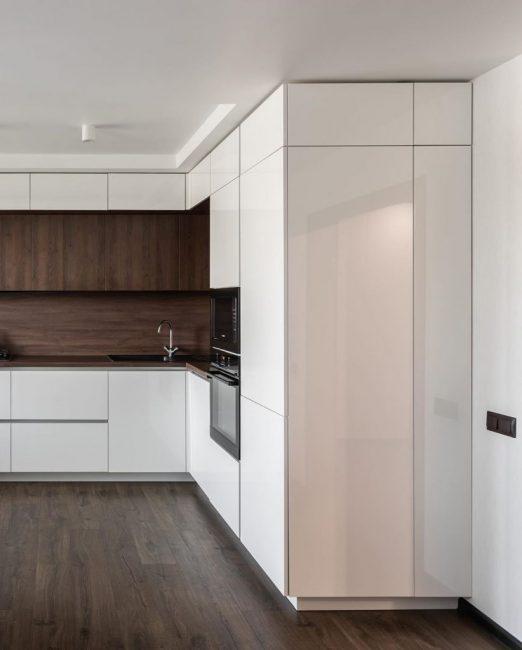 """Практически всю технику решили сделать встроенной. Холодильника не видно совсем, он скрылся в пенале. Микроволновка и духовой шкаф """"утоплены"""" в кухонный гарнитур."""