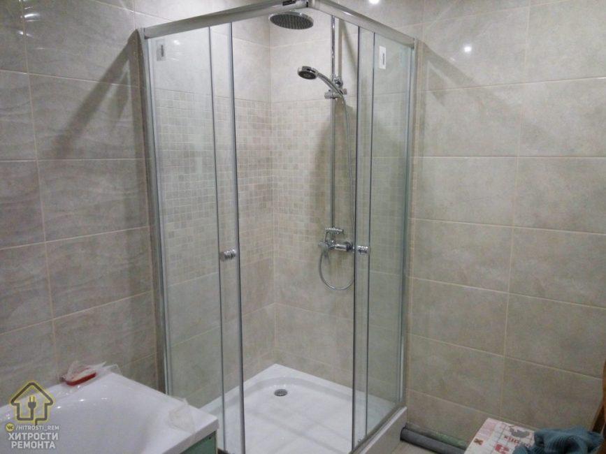 Размер ванной комнаты позволил не только установить ванну, но и поставить душевую кабину. Для нее использовались недорогие материалы. В углу не помешали бы полочки для туалетных принадлежностей.