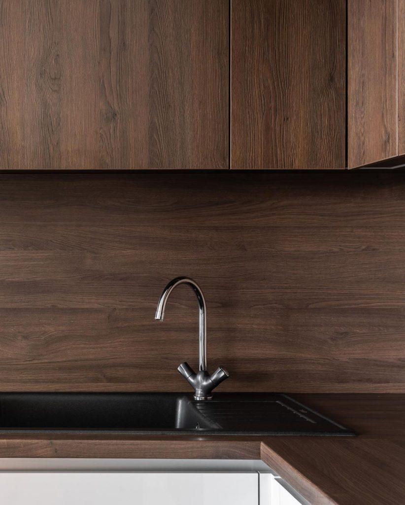 Черная лаконичная раковина находится практически в углу. Так как ее немного сдвинули, это позволит мыть посуду с комфортом.