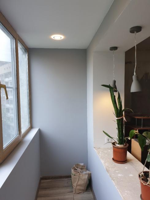 Стены заштукатурили и покрасили в нейтральный серый оттенок. Теперь на лоджии можно поставить кресла и столик для отдыха. Здесь будет тепло круглый год.