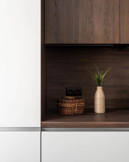 Розетки также сделали черными, чтобы они не выделялись на фоне темного фартука. Милый и лаконичный декор, такой как эта ваза с листьями, как нельзя лучше украшает интерьер.