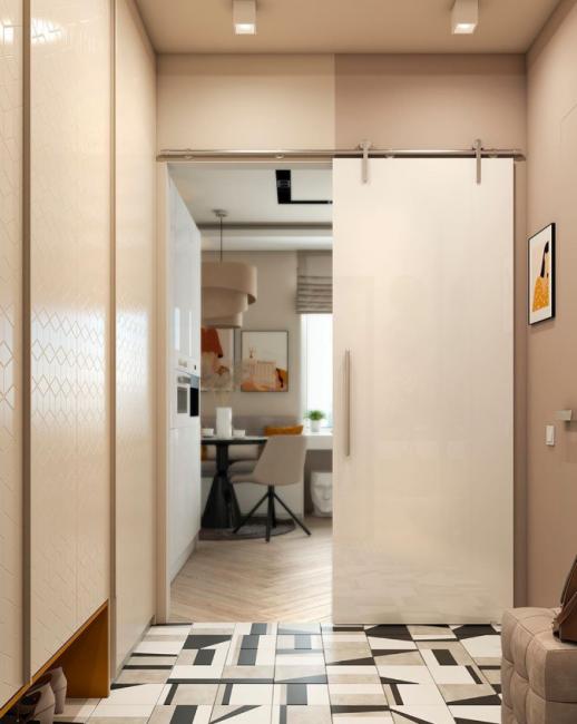 Из коридора в кухню ведет раздвижная дверь. На полу — плитка с оригинальным геометрическим рисунком.