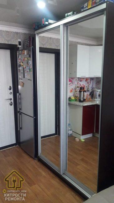 Возле холодильника есть вместительный шкаф-купе с зеркальными дверцами. Здесь легко поместились вещи молодого человека.