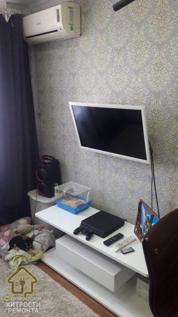 Под телевизором разместилась белая тумба, на которой в клетке живет пушистый любимец хозяина, а также стоит главная вещь холостяка — игровая приставка.